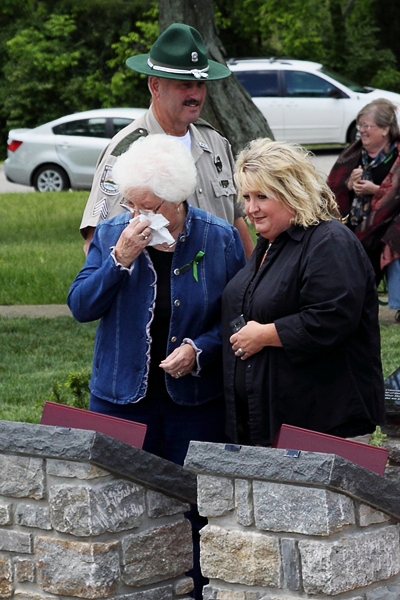 Linda Tabor, widow of Conservation Officer Denver Tabor, wipes away tears as she gazes upon a plaque honoring her late husband. Officials dedicated a memorial to six conversation officers killed in the line of duty during a ceremony held May 17 in Frankfort. Accompanying Tabor is Stacy Hardin Tabor (right). Photo: Kevin Kelly, Kentucky Department of Fish and Wildlife Resources photo by Kevin Kelly