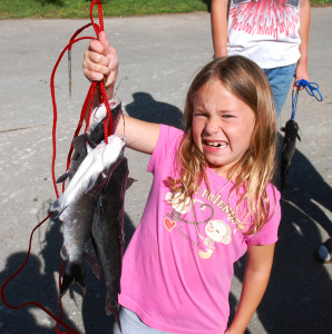 Grace Porter struggles to hold up her stringer of fish. (photo by Chris Erwin)