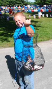 Warren Curtis proudly displays the basket of fish he caught at the Kids Fishing Derby. (Photo by Chris Erwin)