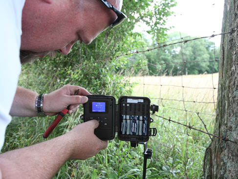 Bo Spencer, information specialist for the Kentucky Department of Fish and Wildlife Resources, adjusts a trail camera on his family farm in Anderson County. Trail cameras give hunters an idea of the game animals living in a particular area while minimizing human disturbance.