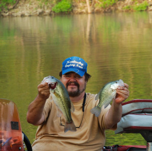Author Chris Erwin holding an Largemouth Bass and a Crappie he caught last week on Cave Run Lake using the method described in last week's column, — crankbaits fishing points and shore lines. (Photo by Scott Erwin)
