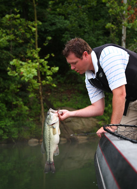 "Chad Miles, host of the ""Kentucky Afield"" television show, holds a 23-inch largemouth bass he caught in June on a Shakey head and straight-tailed worm a few years ago from Nolin River Lake. June is a transitional month for largemouth bass, but those who fish the right areas and depths should catch plenty of fish."