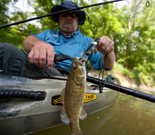 Fish grippers, such as this one used to remove a lure from the mouth of a smallmouth bass prior to release back into Jefferson County's Floyds Fork Creek, are invaluable tools for anglers who want to release their catch in summer. Proper fish handling techniques help fish thrive after release during the hot months.